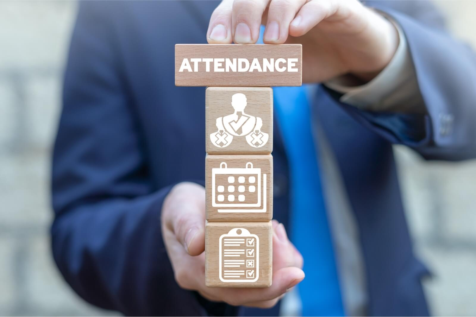 A person is holding wooden cubes that feature attendance tracking